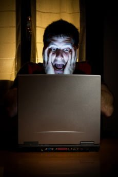 Man Cradling his Head in his hands frustrated with his computer