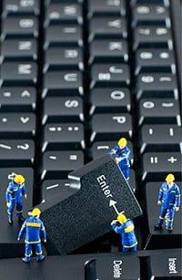 Micro Men pulling apart a black Computer Keyboard